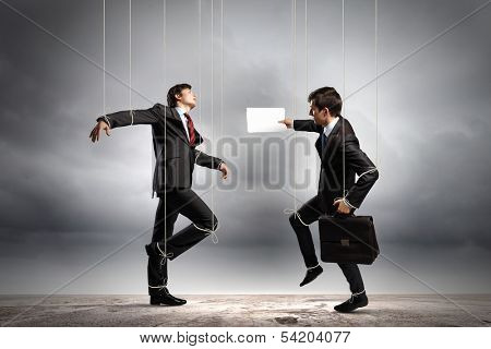 Image of businesspeople hanging on strings like marionettes. Conceptual photography