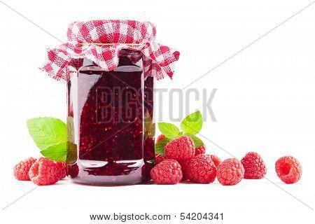 Jar with raspberry jam with raspberries on white