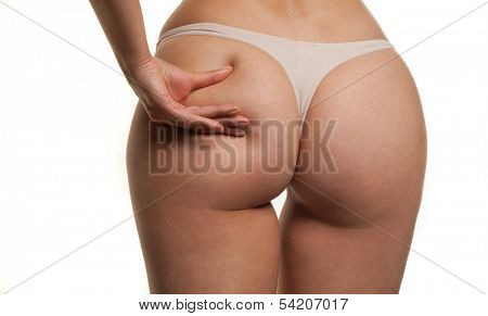 View from behind of a curvaceous sexy womans buttocks in a g-string with her fingers making a seductive gesture by pinching her flesh, isolated on white