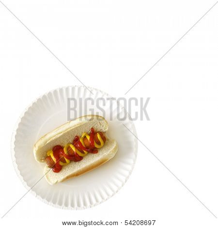 Hot dog on a bun on a white paper plate with ketchup and mustard