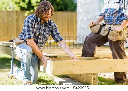 Mid adult manual workers working on wooden frame at construction site