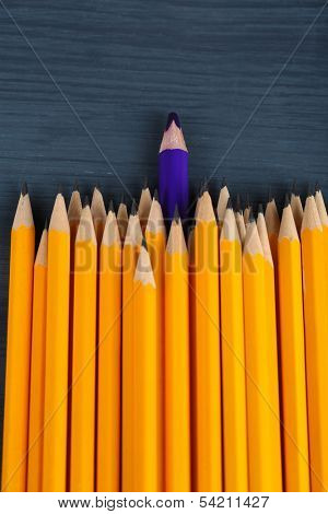 Celebratory pencil among usual pencils, on color background