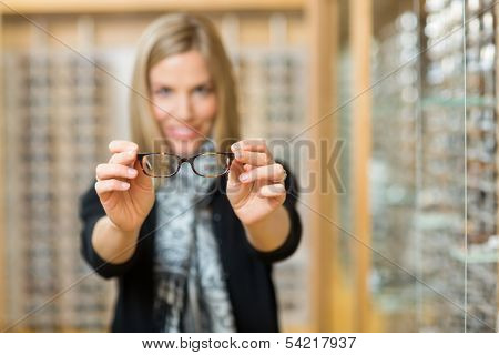 Mid adult woman showing new reading glasses in optician store