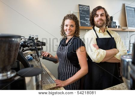 Portrait of confident workers standing at counter in coffeeshop