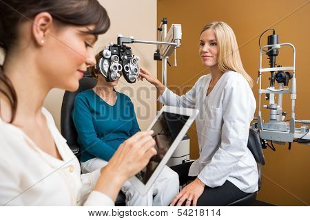Female eye doctor examining senior woman's eyes while colleague using digital tablet in store