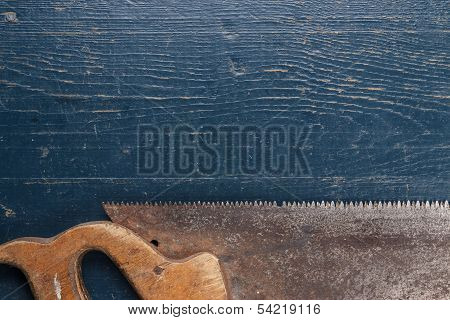 old rusty saw on blue table