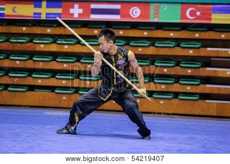 KUALA LUMPUR - NOV 03: Malaysia's Ho Mun Hua performs with a staff in the Men's 'Nangun' Event at the 12th World Wushu Championship on November 03, 2013 in Kuala Lumpur, Malaysia.