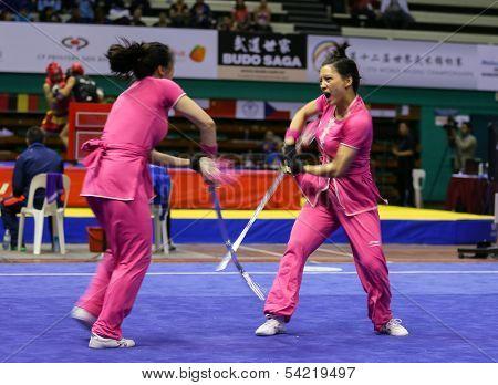 KUALA LUMPUR - NOV 05: Members of Australia's dalian team performs a fight scene in the Women's Dual Event at the 12th World Wushu Championship on November 05, 2013 in Kuala Lumpur, Malaysia.