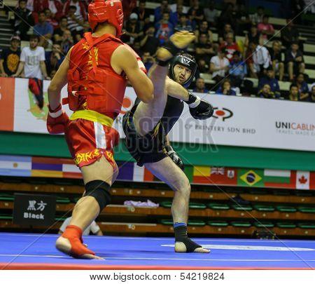 KUALA LUMPUR - NOV 05: Russia's Bektermirov Arslan (black) kicks Iran's Hamidreza Gholipour in the Sanda boxing event, 12th World Wushu Championship on November 05, 2013 in Kuala Lumpur, Malaysia.