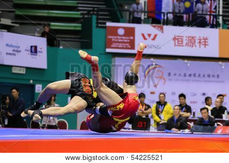 KUALA LUMPUR - NOV 03: Macau's Cai Aolong (red) fights Vietnam's Nguyen Van Tai in the Men's 'Sanda' event of the 12th World Wushu Championship on November 03, 2013 in Kuala Lumpur, Malaysia.