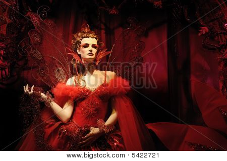 High fashion model in red dress and fantasy setting