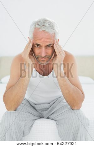 Portrait of a mature man suffering from headache in bed at home
