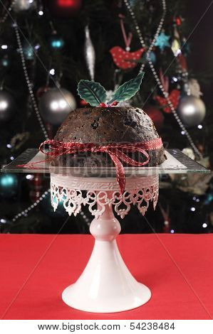 Beautiful Christmas Table Setting In Front Of Christmas Tree, Featuring A Classic Plum Pudding With