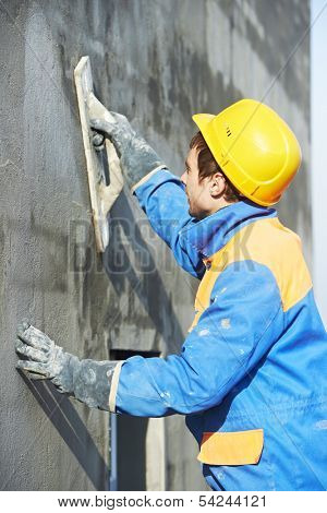 builder at facade plastering work during industrial building with putty knife float