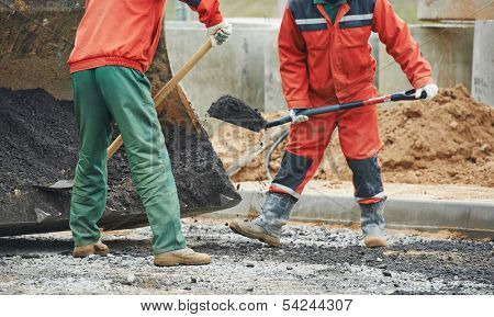 builders workers at asphalting paver machine during Road street repairing works