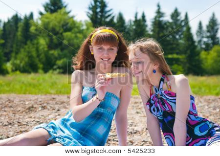 Two Girls On  Meadow Eat A Pizza