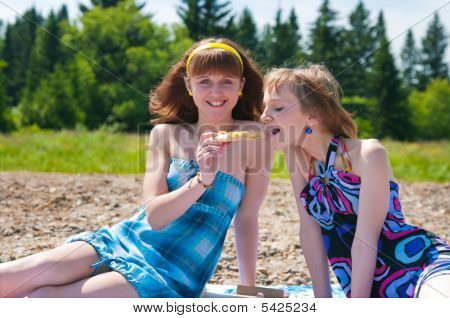 Two Girls On A Meadow Eat Pizza
