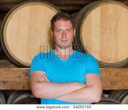 Sommelier With Arms Crossed In The Wine Cellar