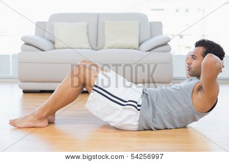 Side view of a young man doing abdominal crunches in the living room at house