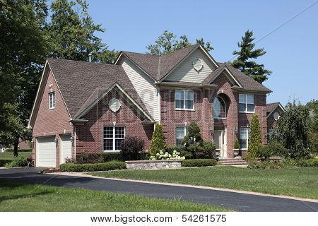 Brick home in suburbs with arched entry
