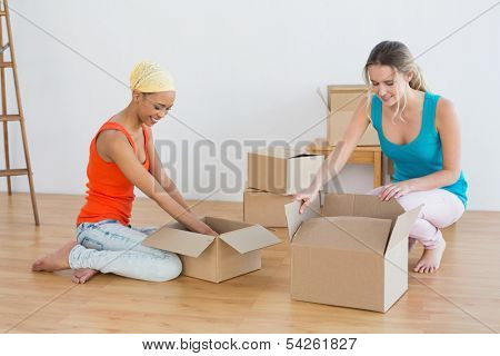 Two happy friends moving together in a new house and unwrapping boxes