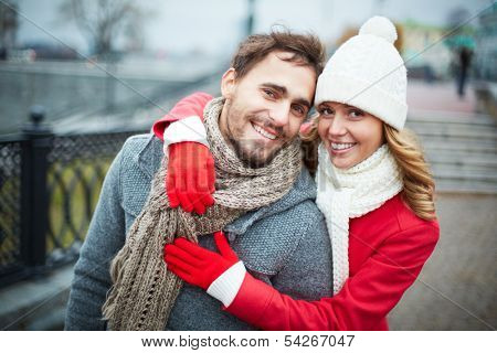 Image of affectionate couple looking at camera in park