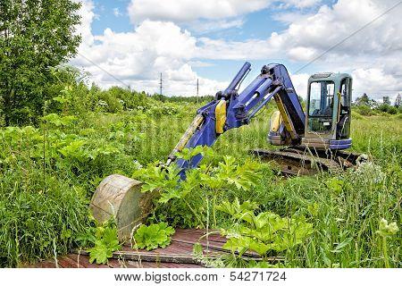 Caterpillar Dredge In The Field Among A Grass
