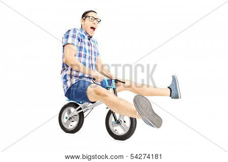 Nerdy young male riding a small bicycle isolated on white background