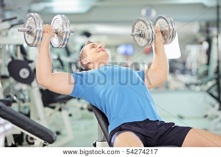 Young muscular man lifting weights in a gym