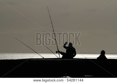 Anglers in silhouette.