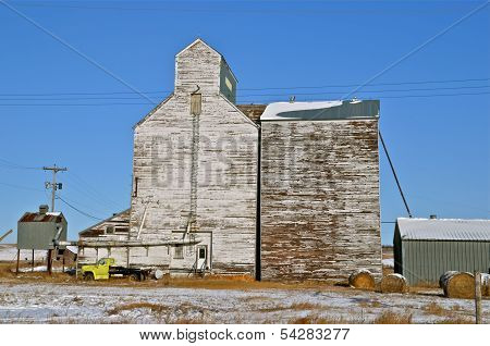 A rural grain elevator stands empty in the snow