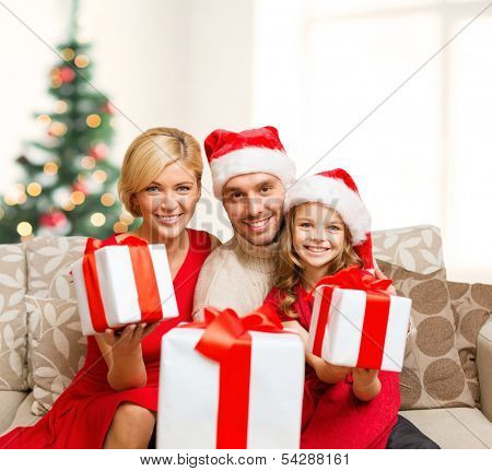 family, christmas, x-mas, winter, happiness and people concept - smiling family in santa helper hats with many gift boxes