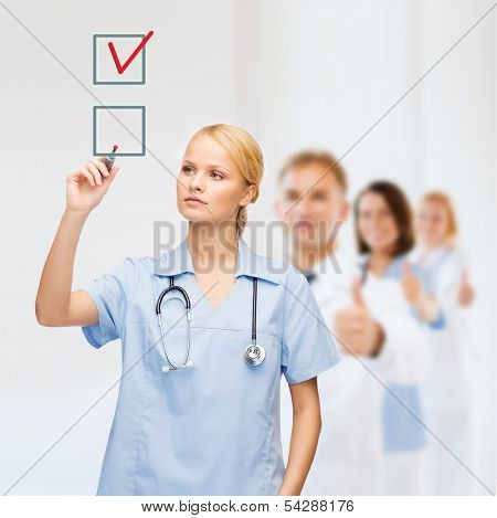 healthcare, medical and technology - young doctor or nurse with marker drawning red checkmark into checkbox with team on the back