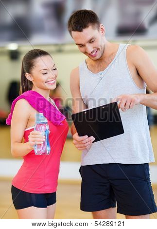 fitness, sport, training, gym and lifestyle concept - smiling male trainer with clipboard and woman with water bottle in the gym