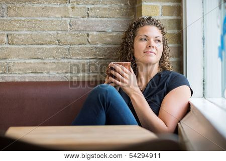 Thoughtful woman holding coffee mug while looking through window in cafe