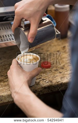 Cropped image of barista making design on cappuccino in coffeeshop