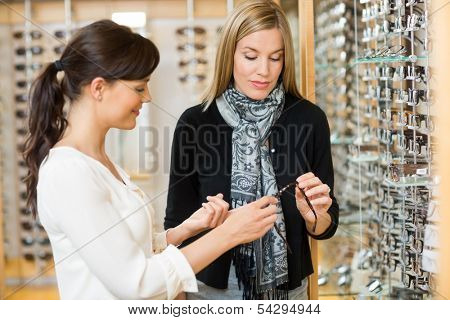 Young woman and female customer holding glasses at store