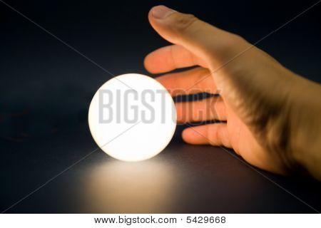 Mão tocando uma bola brilhante