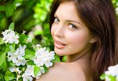 stock photo of nearly nude  - Portrait of pretty girl near the blossomed tree in the park - JPG