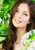 foto of nearly nude  - Portrait of beautiful woman near the flowered tree in the park - JPG