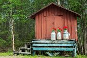 Decoration With Milk Canisters In Front Of Small Barn In Finnish Lapland.