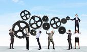 stock photo of cogwheel  - Conceptual image of businessteam working cohesively - JPG