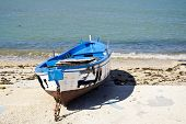 Blue burnt boat on the seashore