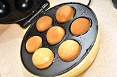 stock photo of cake-ball  - Cooked round cake balls in a counter top baking machine - JPG