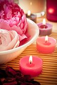 stock photo of oregano  - A bowl full of beautiful pink aromatherapy flowers with candles. Spa scene.