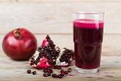 stock photo of pomegranate  - Red pomegranate juice in a glass near a fruit pomegranate and half of pomegranate on wooden background - JPG