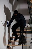 stock photo of creeping  - Burglar with a crowbar and bag creeping on stairs - JPG