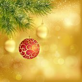 Festive traditional golden Christmas background with hanging baubles, blurry lights and fir twigs fo