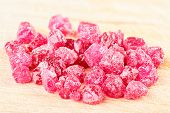 stock photo of uncut  - A pile of raw uncut ruby crystals on wood - JPG