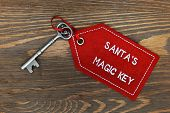 Santa's magic key on a rustic wooden background.